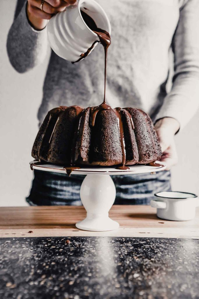 side angle of shiny chocolate glaze being drizzled over a chocolate bundt cake