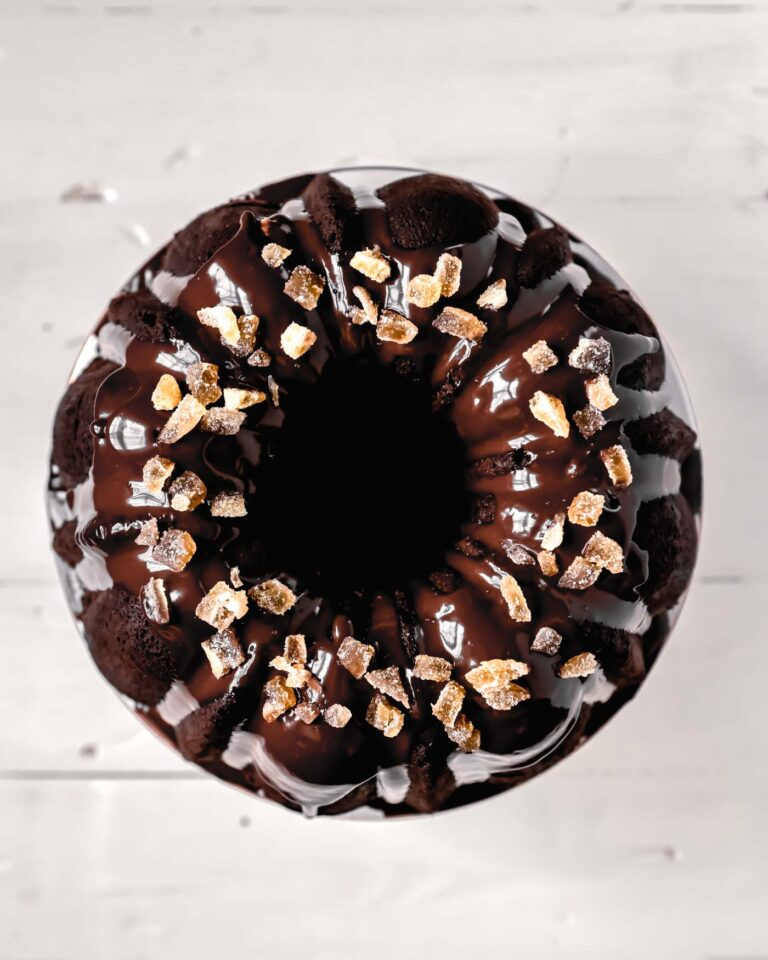 Overhead image of a chocolate bundt cake with a shiny chocolate glaze and candied ginger