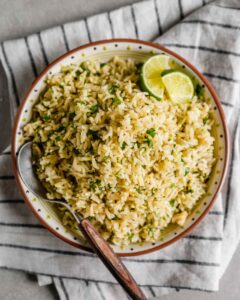 overhead image of brown rice with chopped cilantro and lime wedges in a shallow Mexican-style bowl