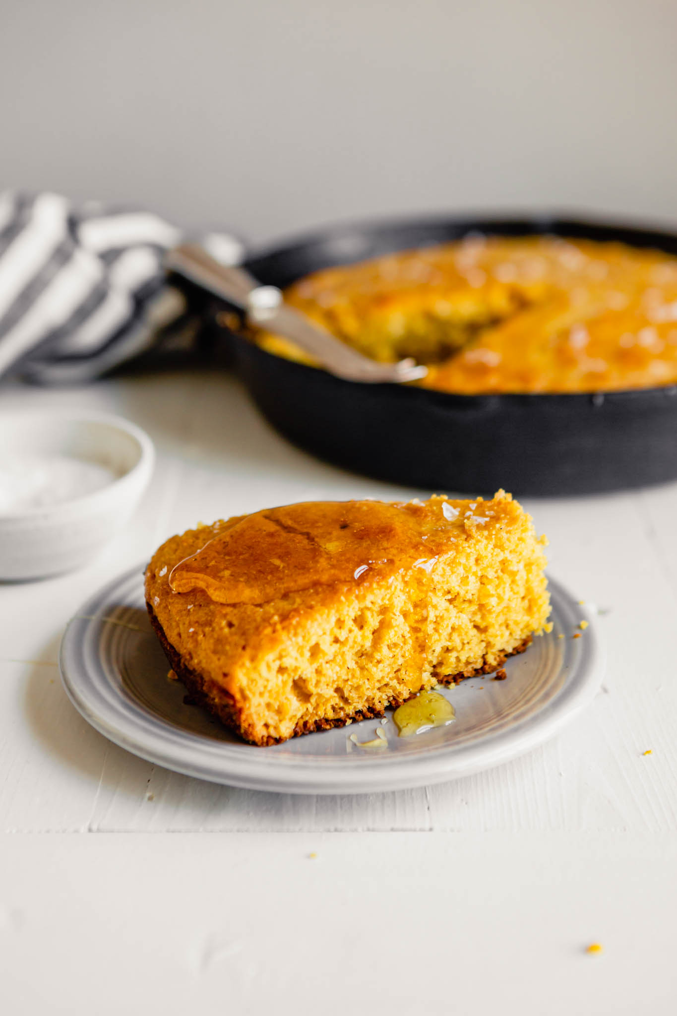 Side angle of honey dripping down a slice of cornbread