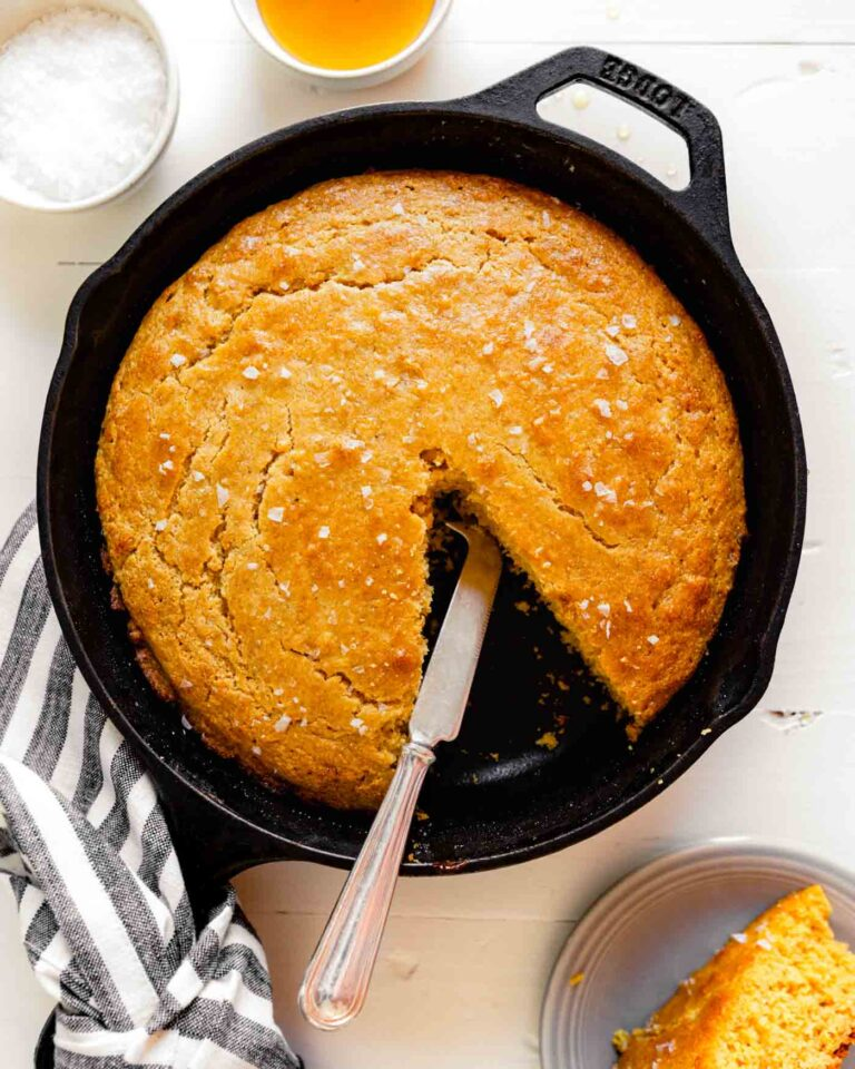 Overhead image of healthy cornbread in a cast iron skillet set on a wooden white table with a bowl of salt and honey to the top right