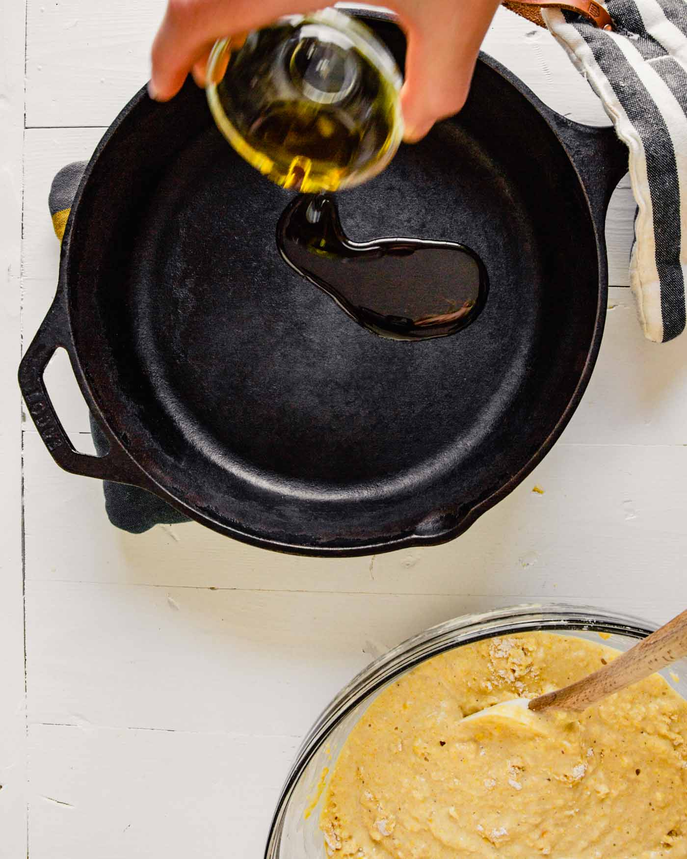 image of oil being poured into a hot cast-iron skillet