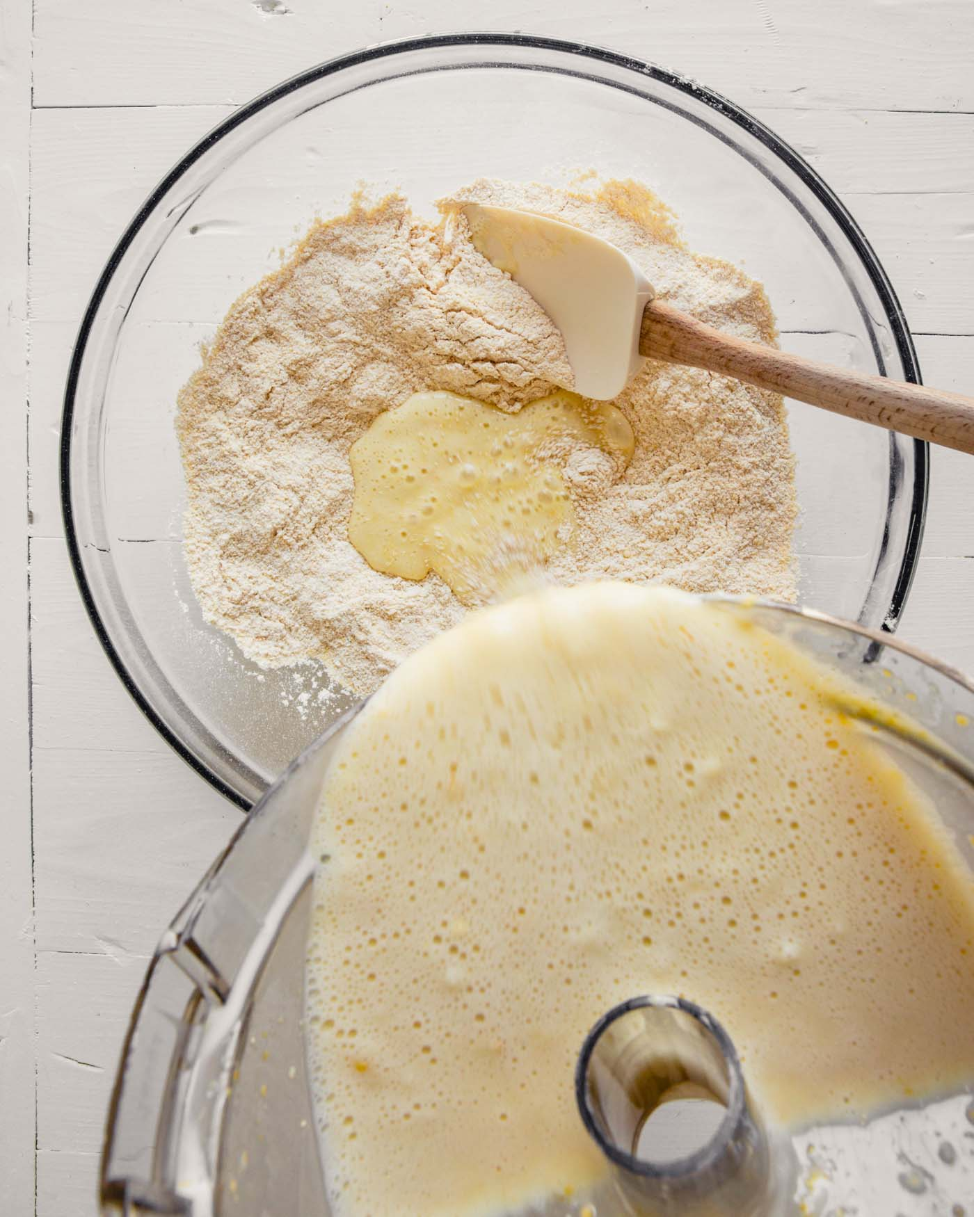 Overhead photo of wet ingredients being poured into dry ingredients for healthy cornbread