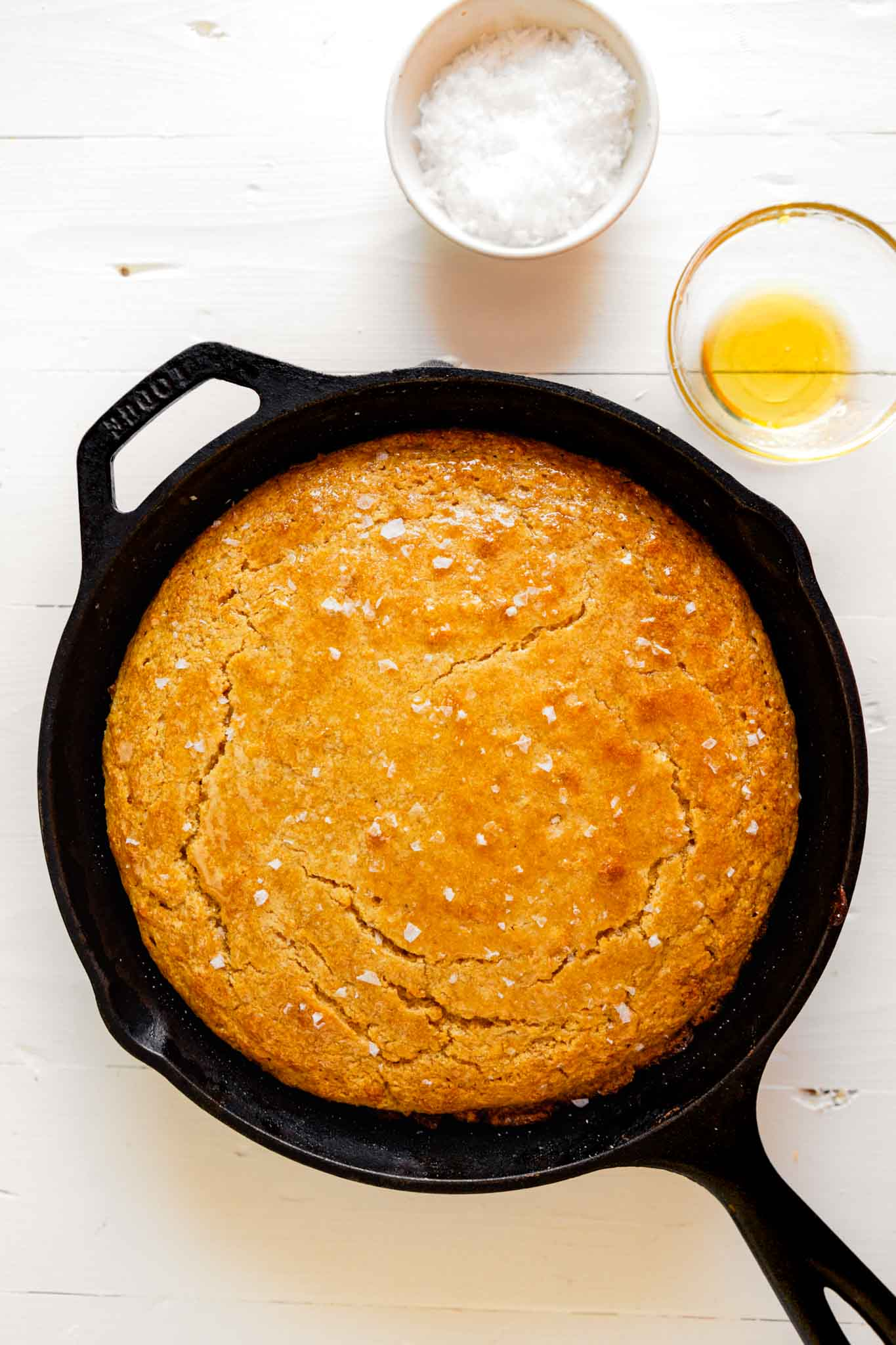 overhead photo of skillet cornbread on a white wooden table with honey and sea salt off to the side