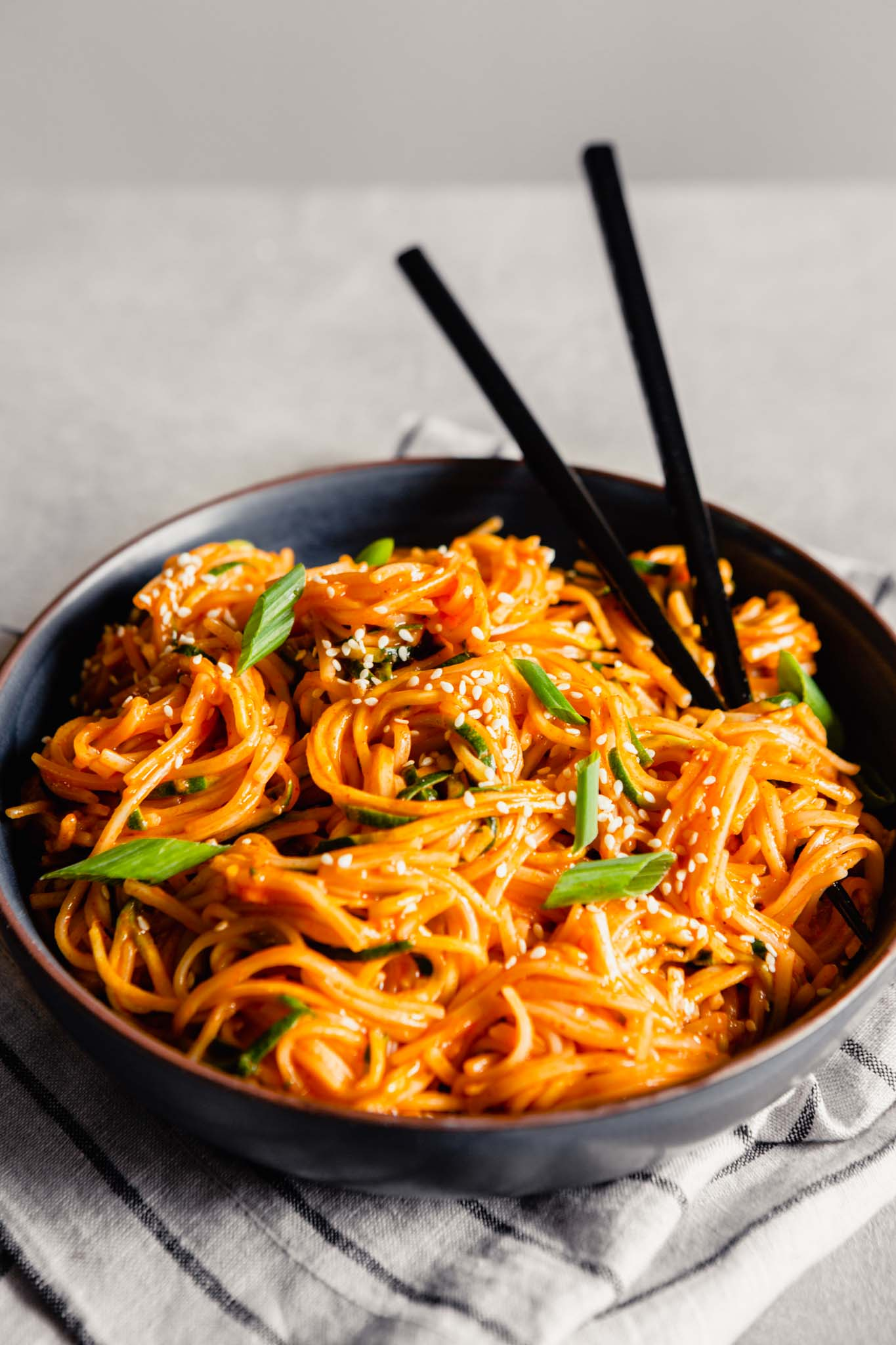 Side angle of bright orange gochujang noodles in a blue bowl with chopsticks sticking out