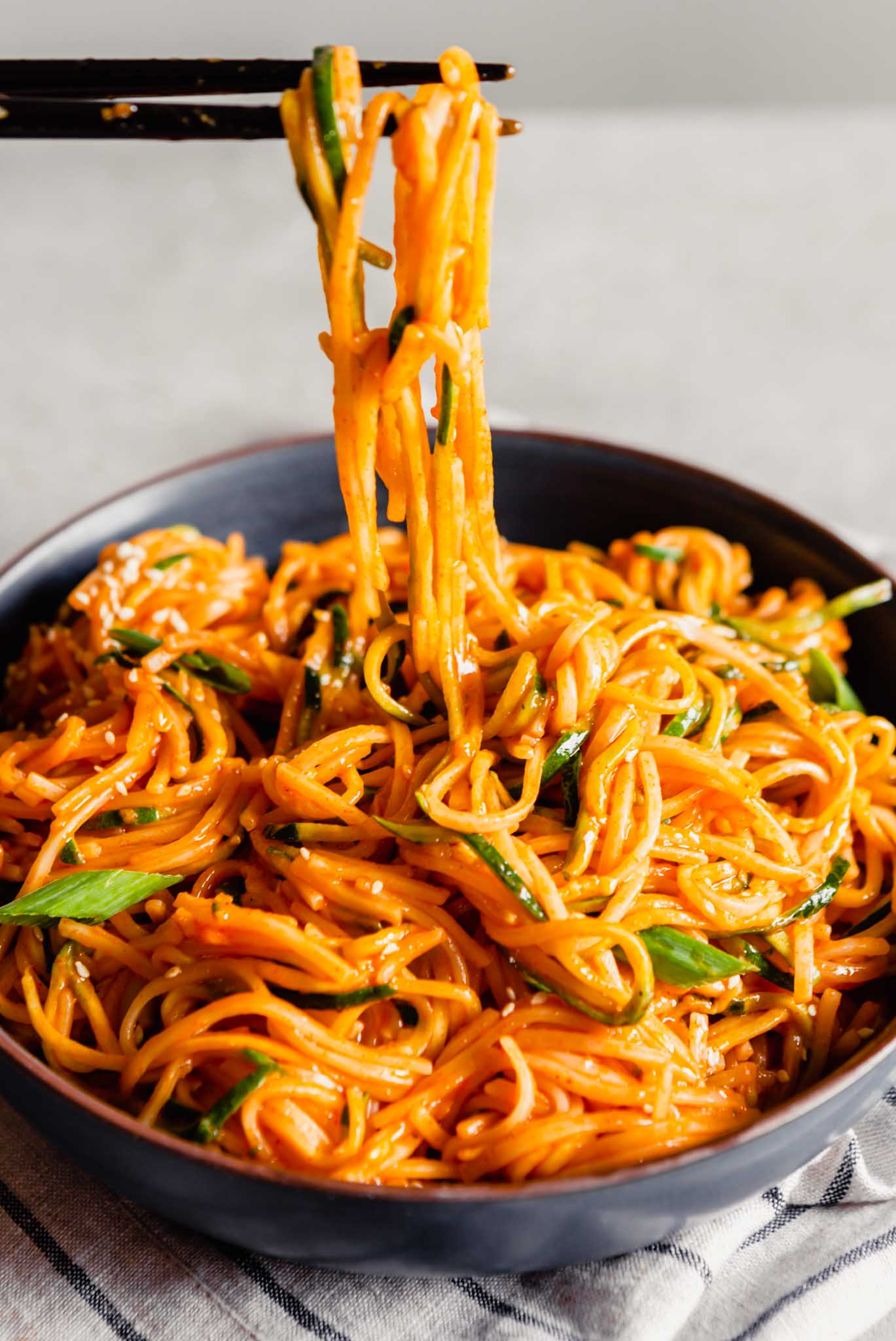 photo of chopsticks pulling a pile of bright orange gochujang noodles up from a bowl