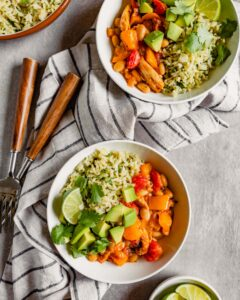 Overhead image of two round white bowls filled with brown rice, a saucy veggie mixture, diced avocado and lime wedges.