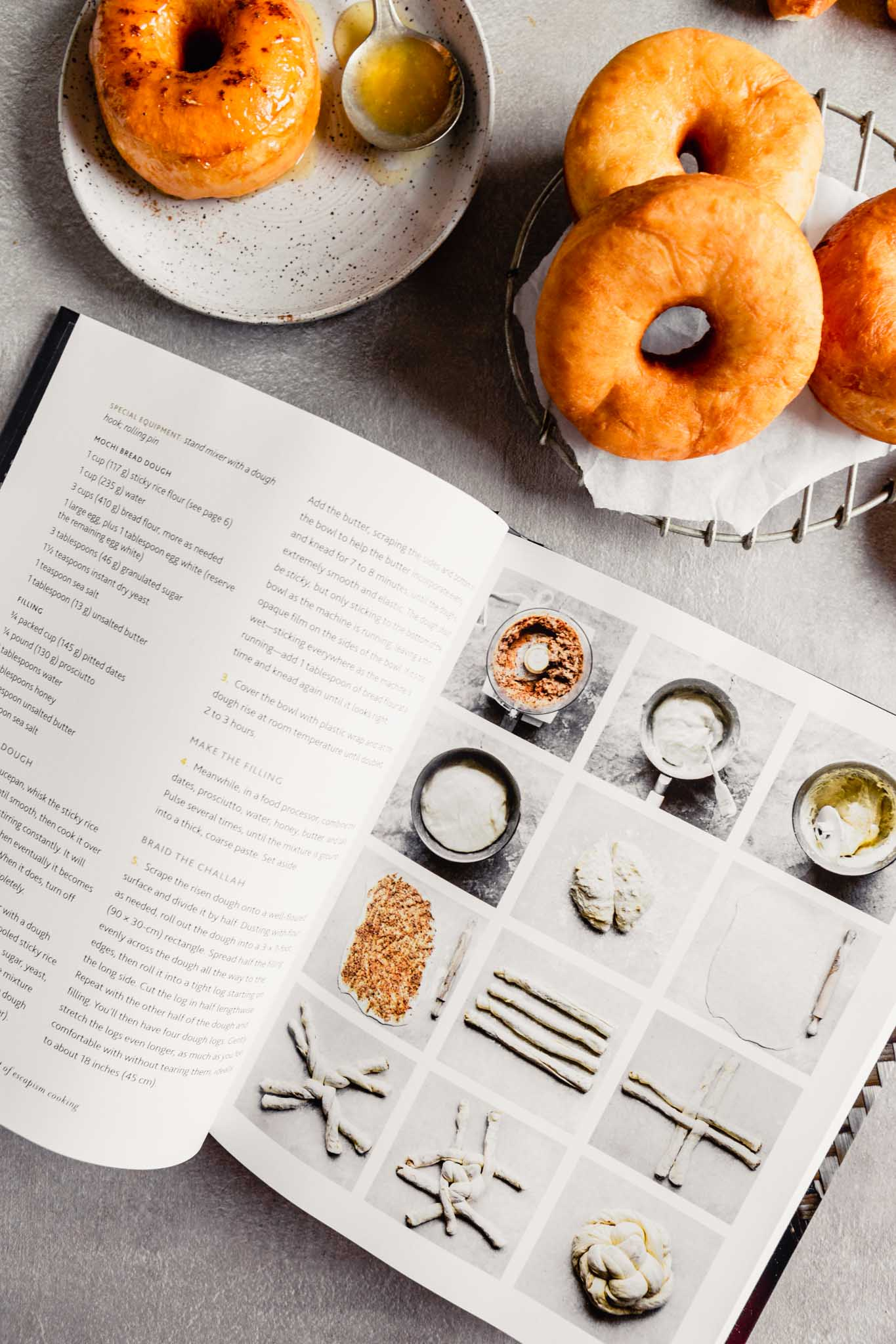 Overhead image of an open cookbook with doughnuts set around it