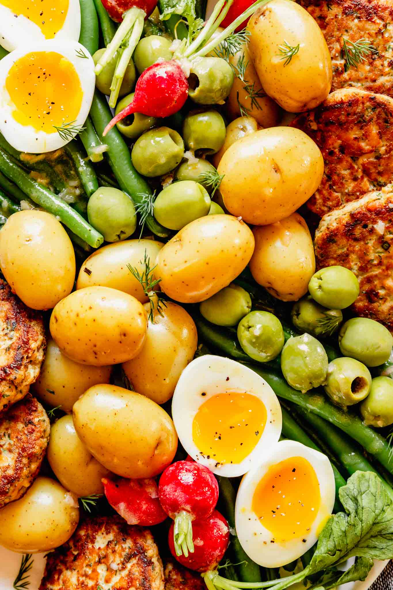 Close up photo of a nicoise salad featuring green beans, soft boiled eggs, salmon cakes, olives, radishes, and gold potatoes.