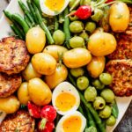 Overhead photo of nicoise salad on a white plate with salmon cakes arranged around the edges of the plate.