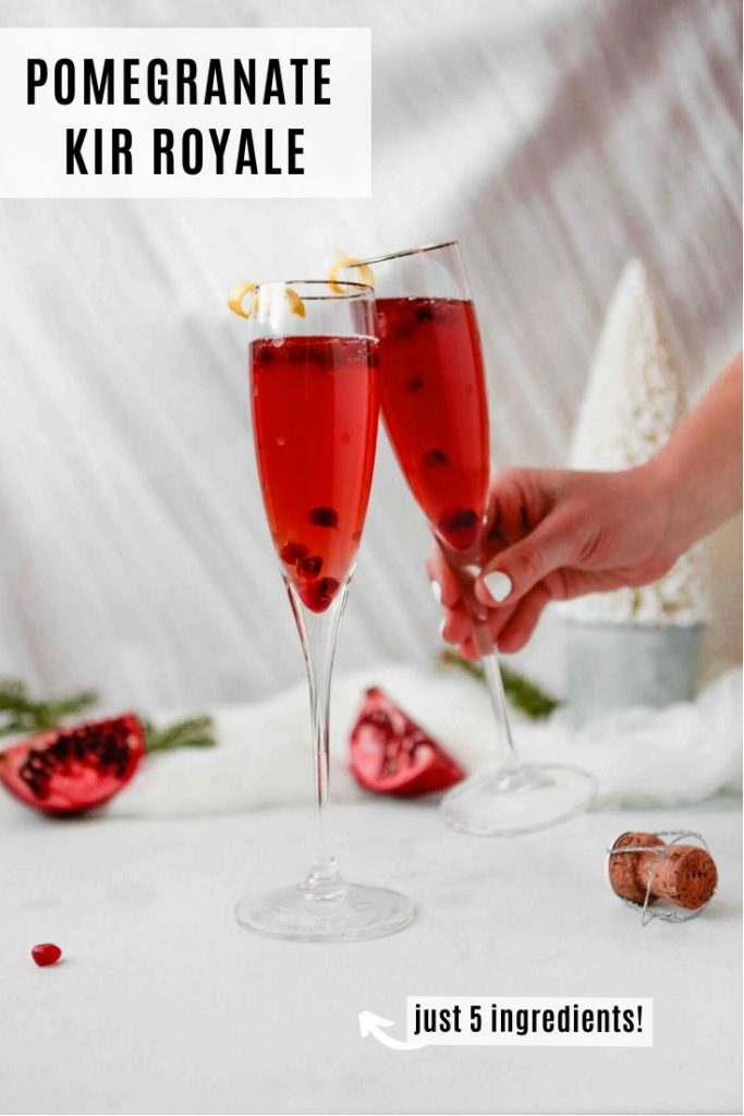 two champagne flutes filled with a red cocktail set on a white table with a white background