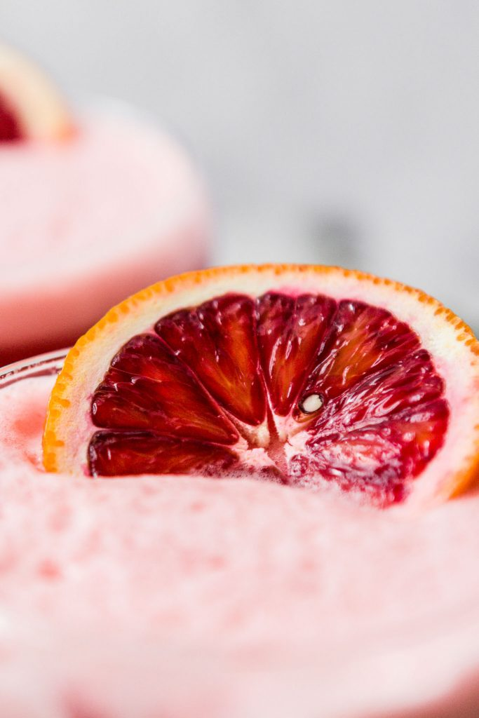 close up image of a blood orange slice on top of a foamy cocktail