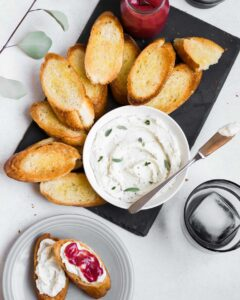 Overhead image of crostini stacked on a gray slate plate with whipped riccotta and cranberry curd set off to the side