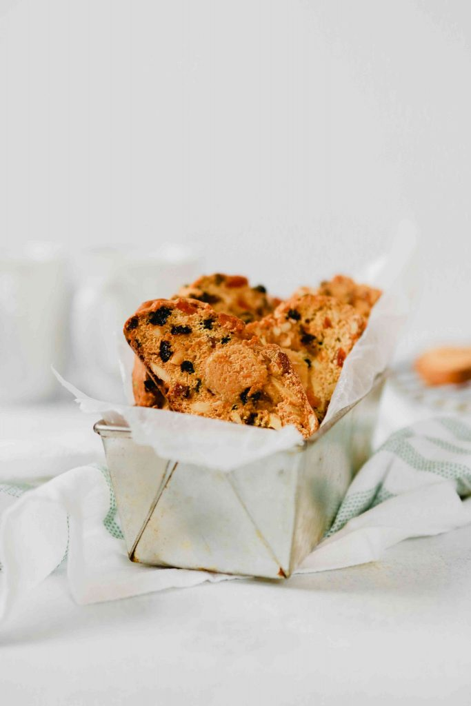stollen biscotti piled into a metal baking pan with white parchment paper