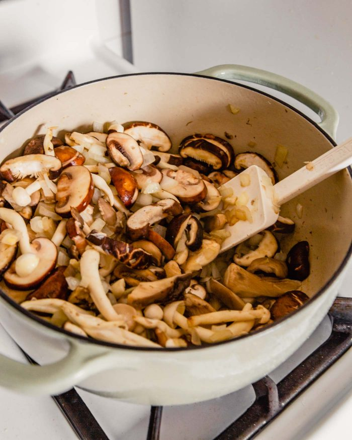 Fresh cut mushrooms in a pot with onions