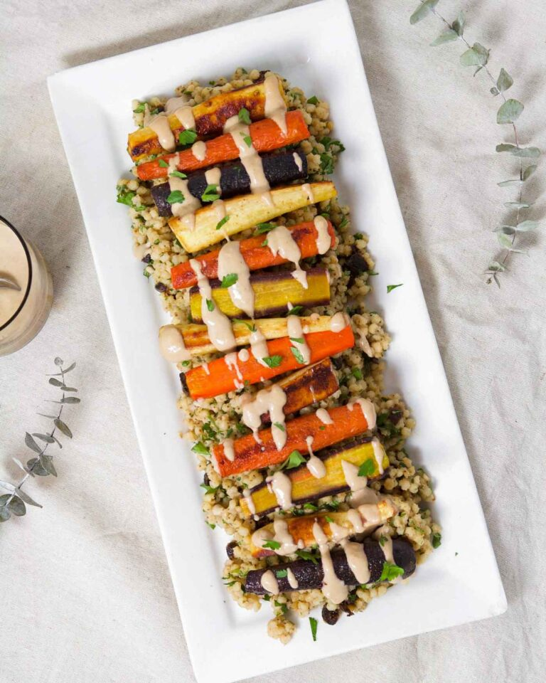 Roasted Root Vegetables layered over a sorghum pilaf on a long rectangular white plate.