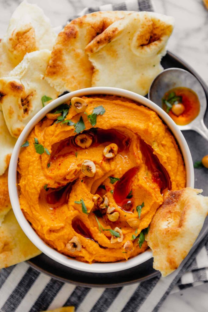Overhead image of orange hummus spread into a white bowl set on a gray plate on a marble table with fresh naan bread.
