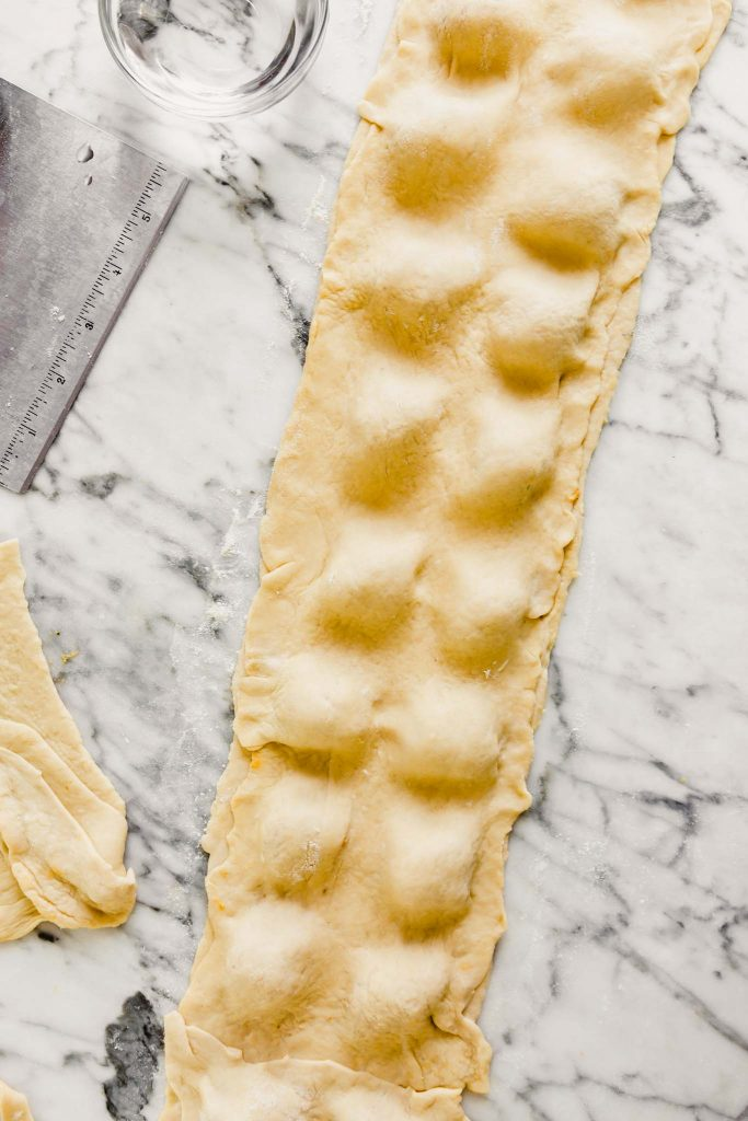 a long rectangle of dough covering pockets of filling to make ravioli
