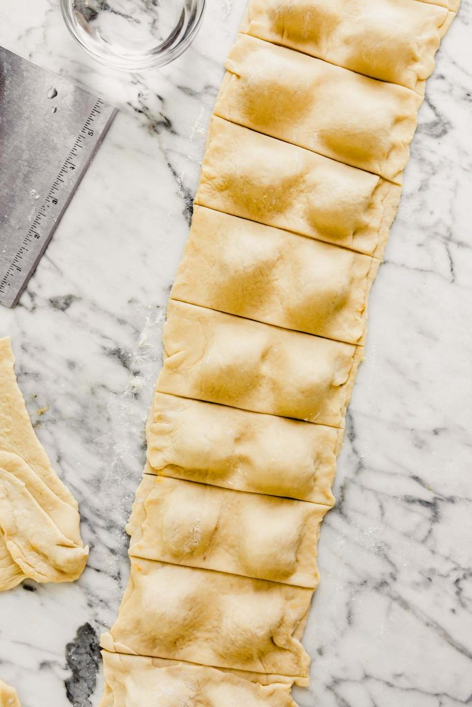 ravioli being cut from a long rectangular piece of dough