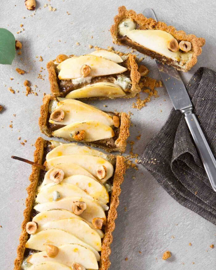 Overhead image of a tart sliced and laying on a gray table with a knife off to the side