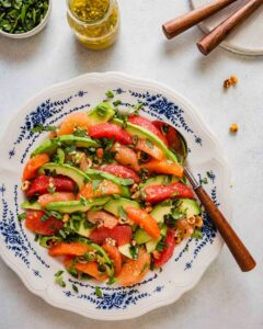 Overhead image of slices of grapefruit, oranges and avocados arranged on a white and blue plate topped with herbs and nuts. Plates, herbs and vinaigrette set off to the side.