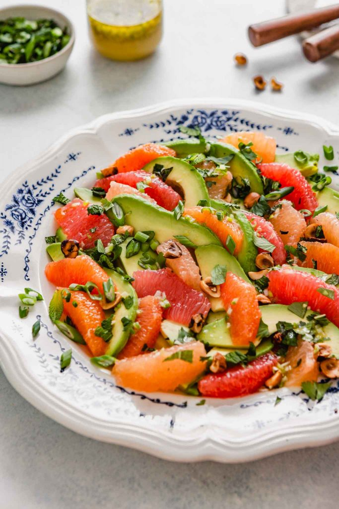 Side angle of slices of avocado, oranges and grapefruit arranged on a white and blue plate with herbs and nuts scattered over top