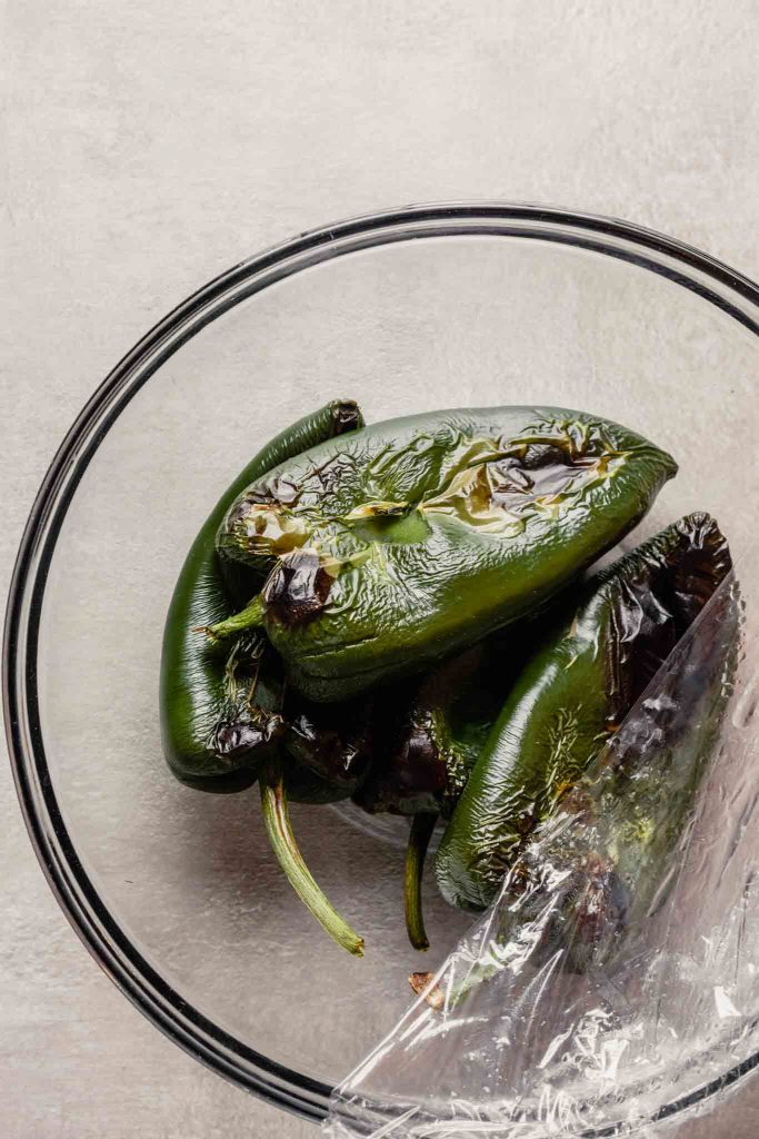 Overhead image of roasted and steamed poblano chiles in a glass bowl