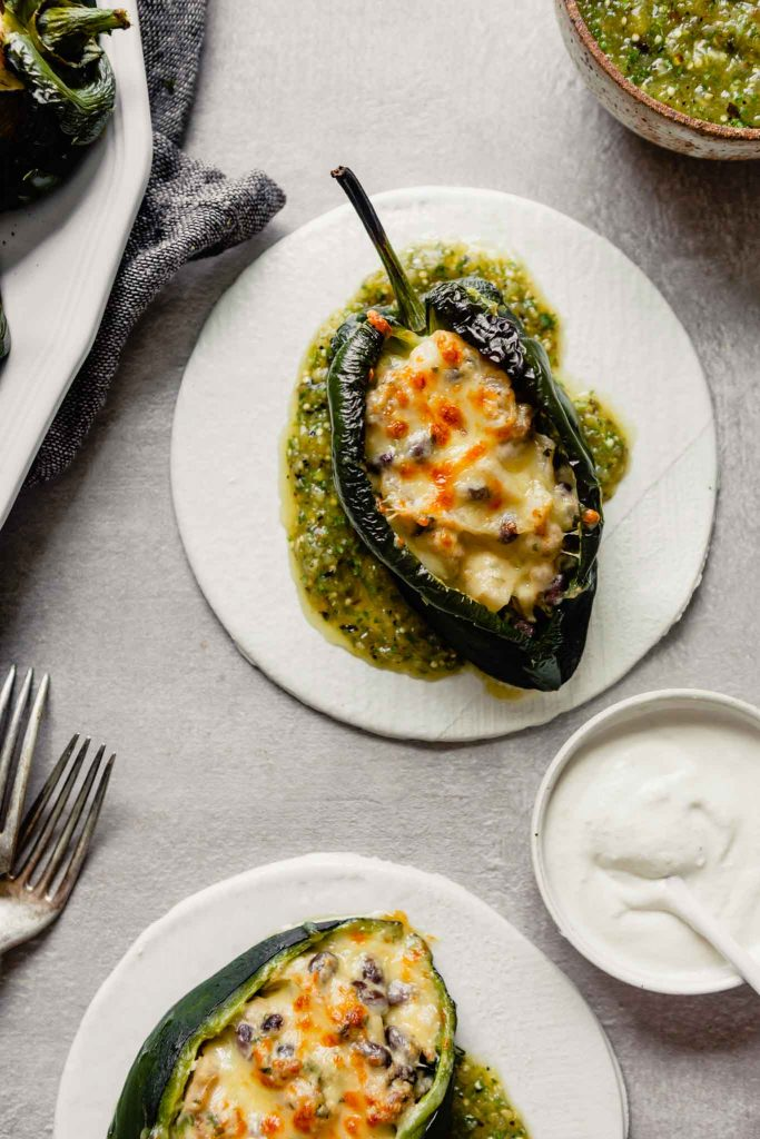 Overhead image of stuffed poblano peppers on white plates set on a gray background with salsa in a bowl off to the side