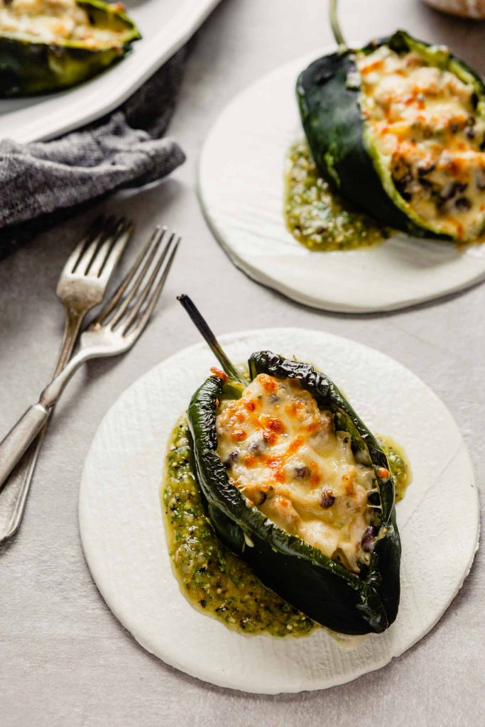 image of stuffed poblano peppers on white plates set on a gray background with salsa in a bowl off to the side