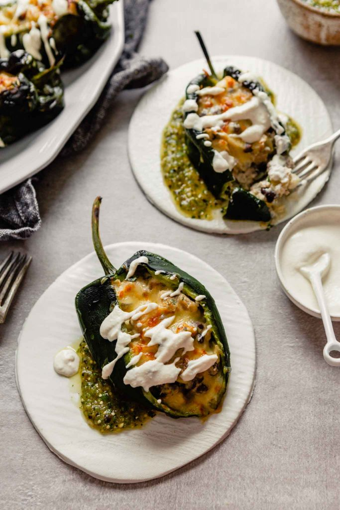 Image of stuffed poblano chiles on white place with a platter of chiles in the background and some salsa off to the side