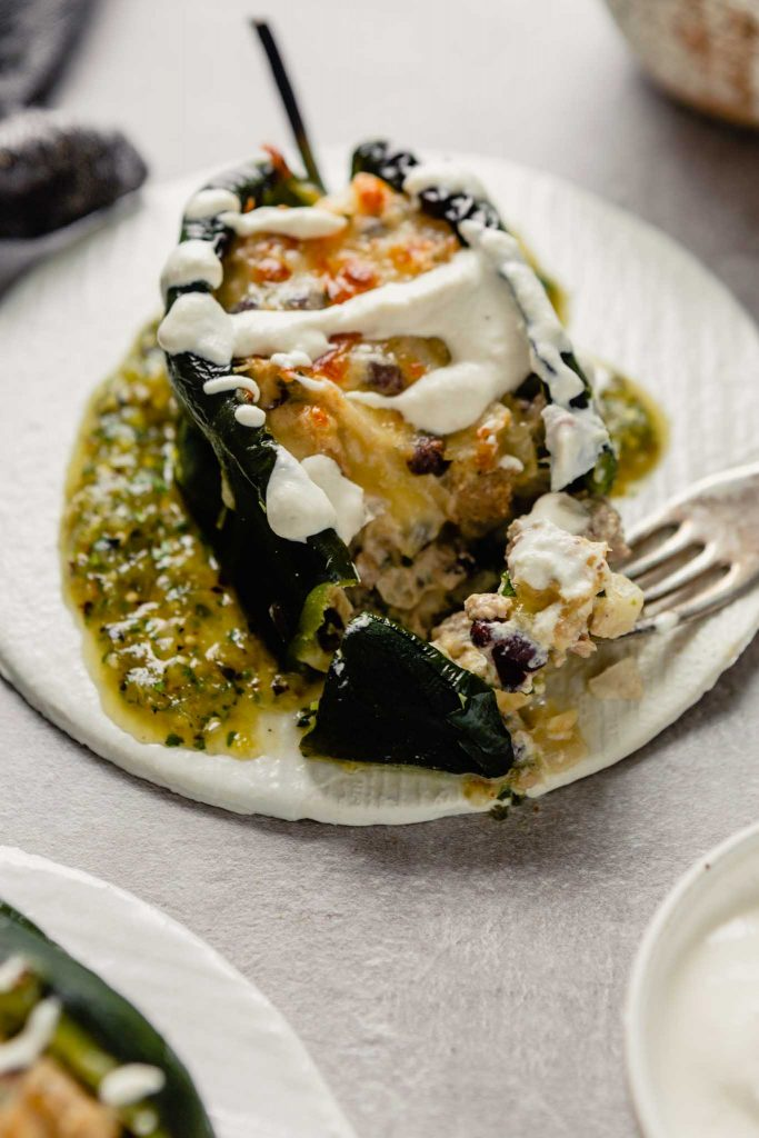 Close up image of a stuffed chile relleno on a white plate with a fork scooping up filling