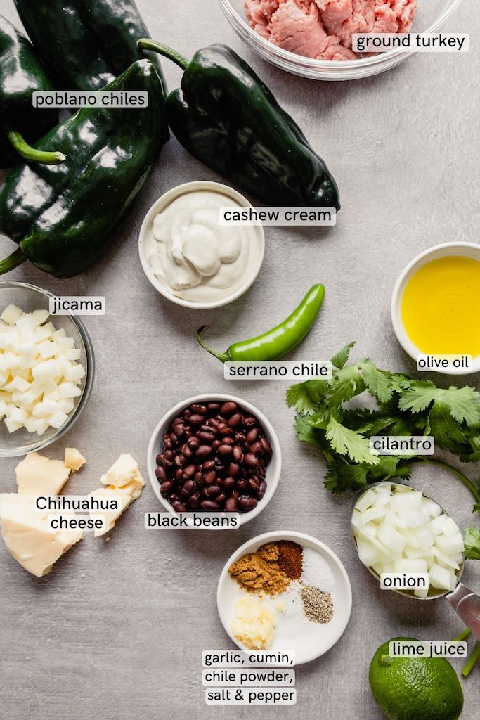 Overhead image of chiles relleno ingredients arranged on a gray table