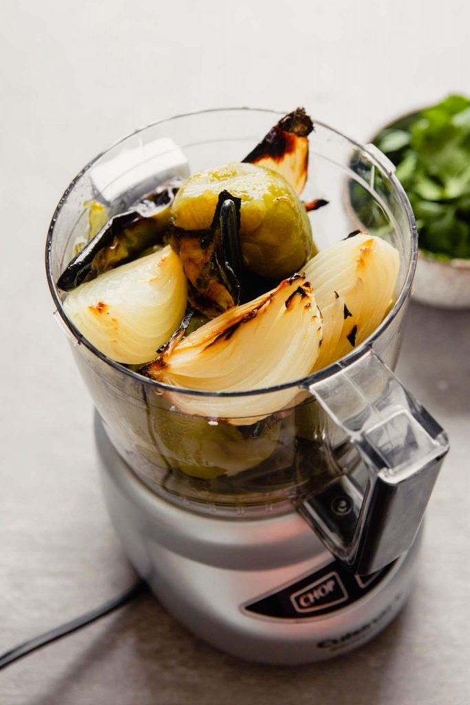 Charred onions and tomatillos in a mini food processor set in a gray table.