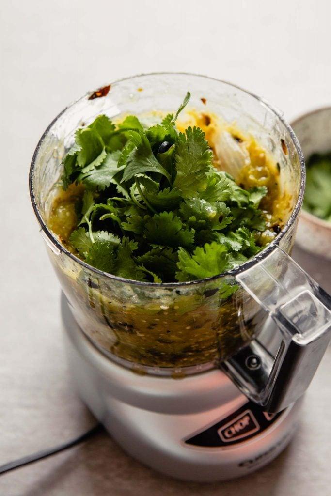 Charred onions, tomatillos, and fresh cilantro in a mini food processor set in a gray table.
