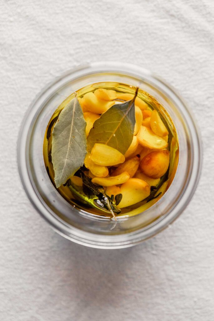 Overhead image of garlic cloves and bay leaves in a jar covered with oil