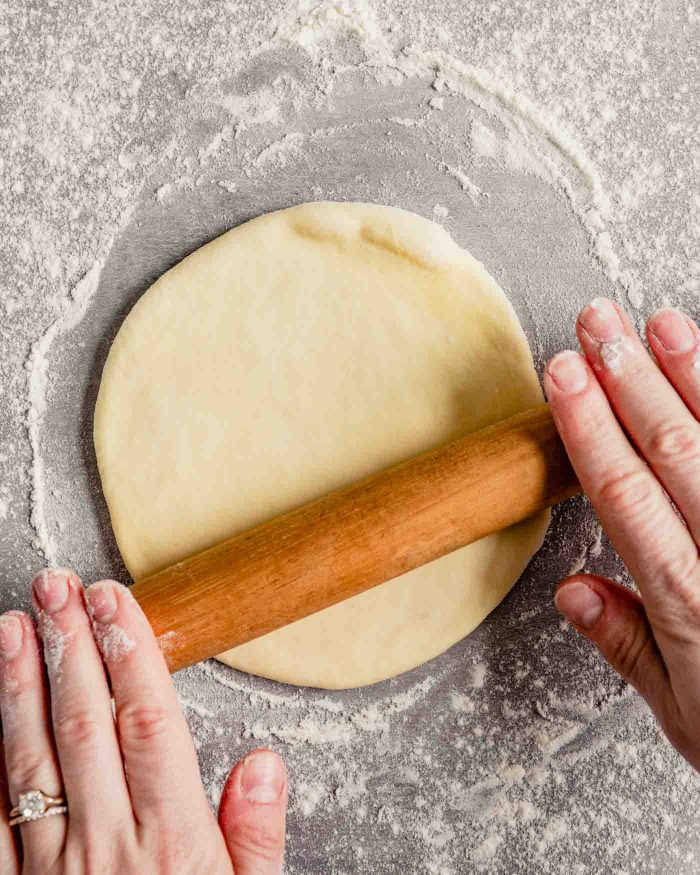 Overhead image of someone rolling out a piece of dough on a lightly floured surface