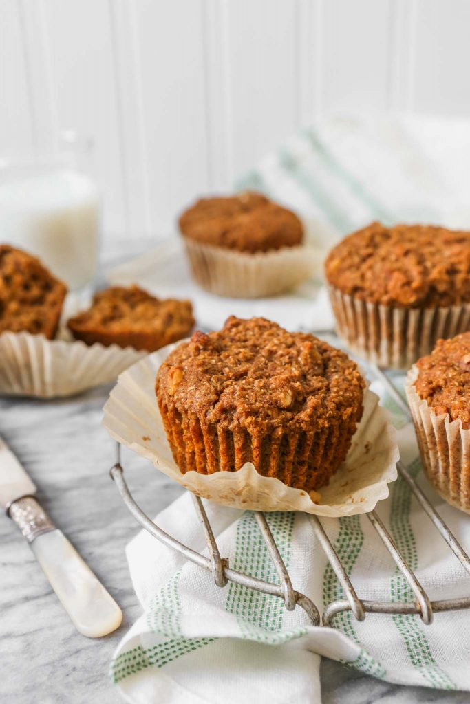 Bran muffins set on a wire rack on a marble table