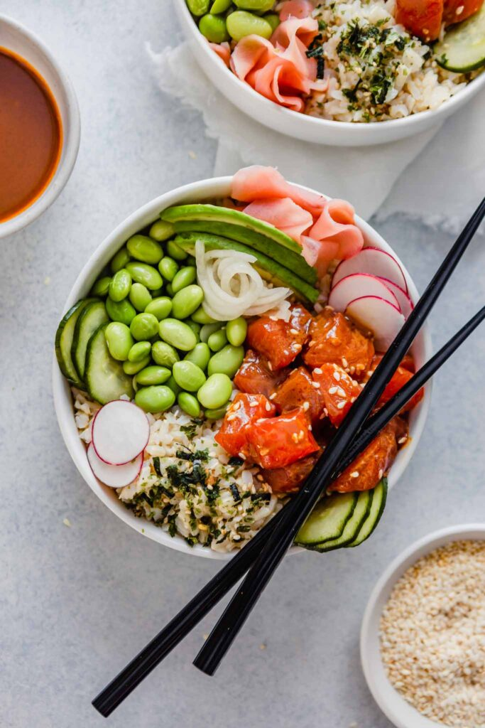 Overhead image of a bowl filled with raw salmon, edamame, cucumbers, ginger and avocado set on a blue table with bowls of sauce and chopsticks