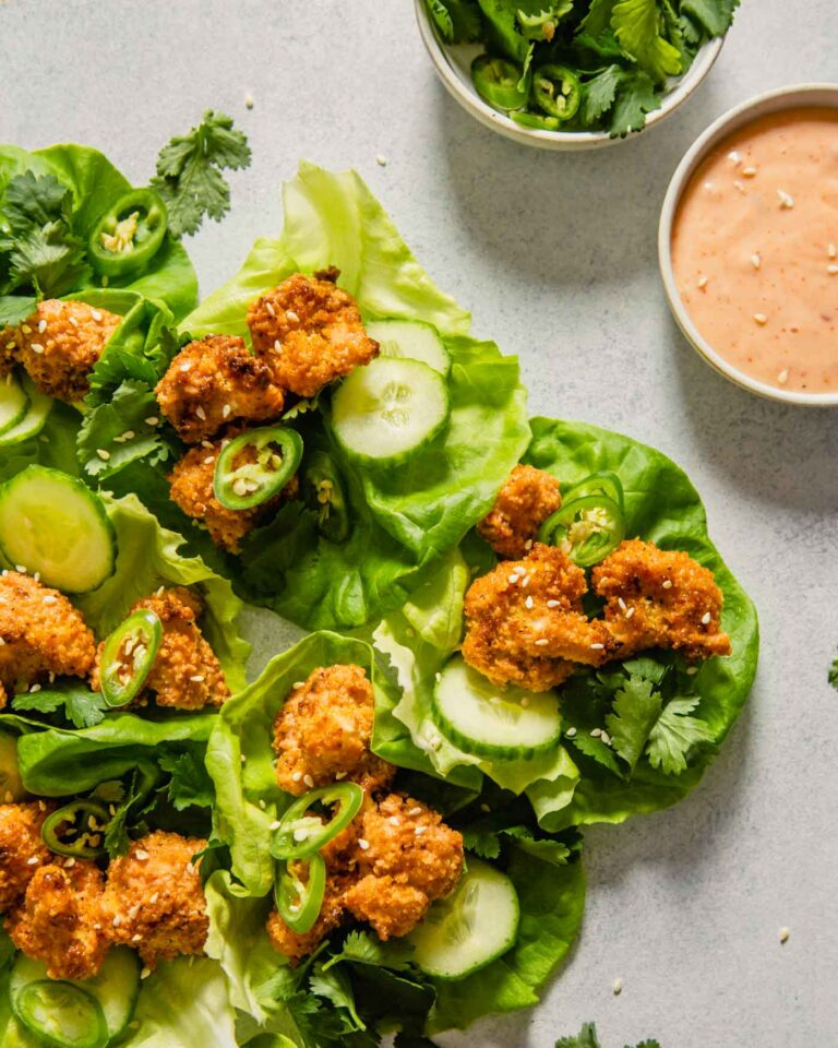 Overhead image of lettuce wraps stacked up along eachother on a light blue table. Lettuce wraps are filled with coated cauliflower, cucumbers, serranos and sesame seeds.