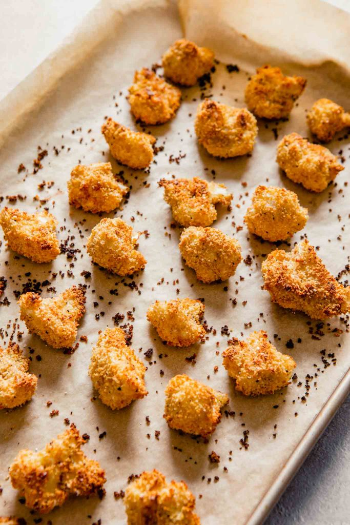 image of crispy baked cauliflower bites in a parchment paper-lined baking sheet