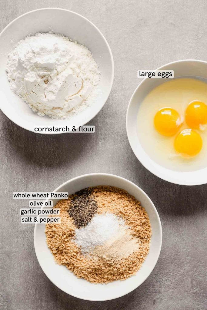 overhead image of three bowls laid out on a gray counter. one bowl has bread crumbs, another has flour and the third has eggs in it.