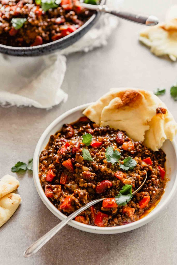 side angle mage of a lentil and bean stew in a white bowl set on a gray table with naan bread stuck in the bowl