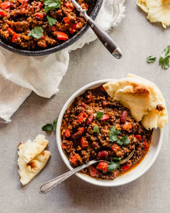 overhead image of a lentil and bean stew in a white bowl set on a gray table with naan bread stuck in the bowl. Large black serving bowl with more lentils in it off to the top left