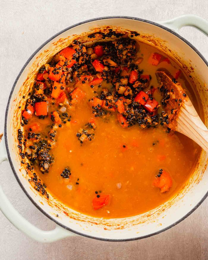 overhead image of veggies and uncooked black lentils covered with vegetable broth