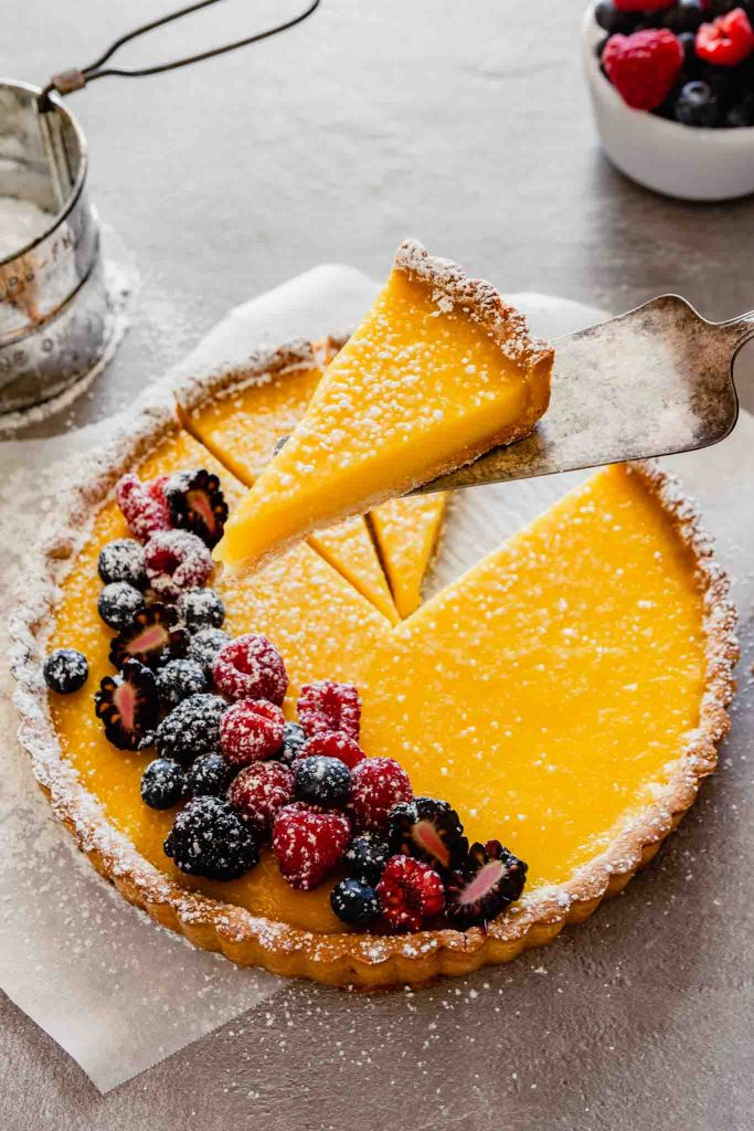 side angle of a piece of lemon tart being held up on a spatula
