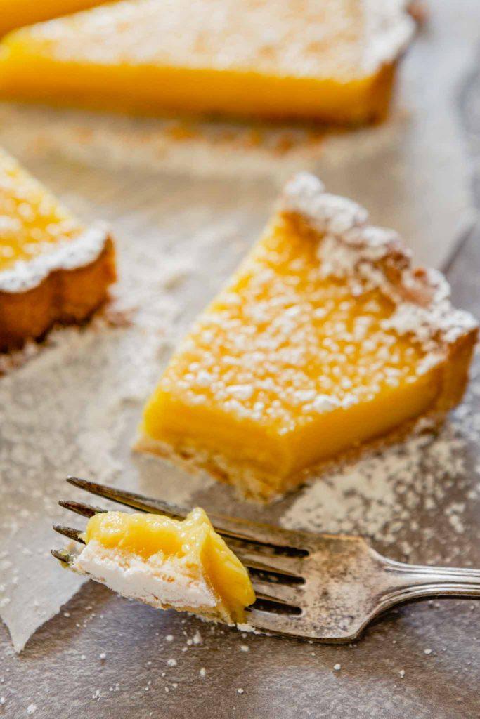 close up image of a bite of lemon tart on a fork