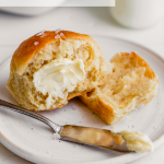 Side angle image of a milk roll topped with butter set on a plate