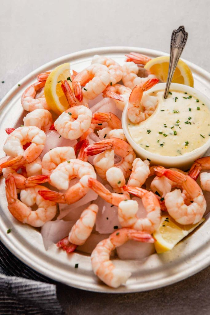side angle image of a metal plate filled with ice, shrimp, and a butter sauce in a white bowl