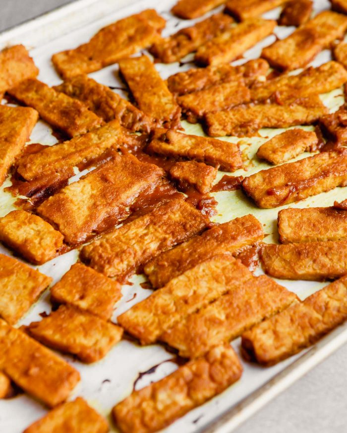 tempeh coated in bbq sauce and baked on a parchment-lined baking sheet