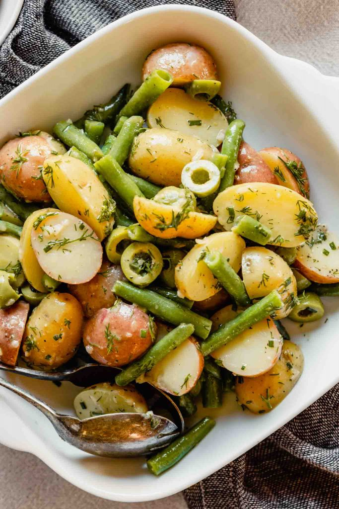 Overhead image of green beans, potatoes, lives and herbs in a white square dish set on a table.